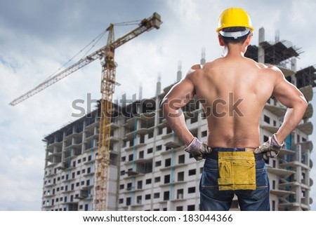 a rear view of construction worker showing his muscles with building construction site - stock photo