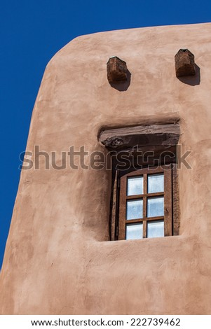 A recessed window in a traditional southwestern building with support beams and curved corners. - stock photo