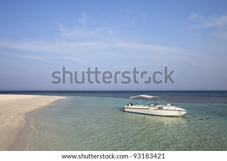 A recreational white boat on lagoon front beach of paradise island - stock photo