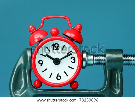 A red alarm clock placed in a Grey clamp against a pastel blue background, asking the question do you manage your time effectively? - stock photo