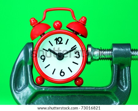 A red alarm clock placed in a Grey clamp against a pastel green background, asking the question do you manage your time effectively? - stock photo