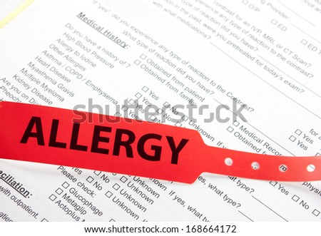 a red allergy patient bracelet on top of a hospital questionnaire paperwork