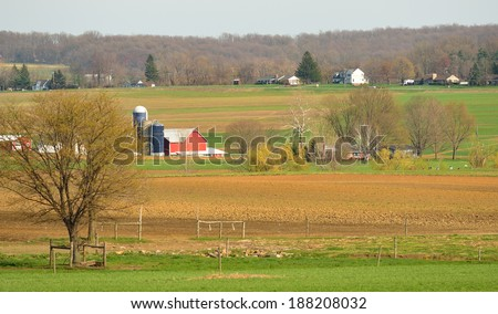 A red Amish farm and barn sits among the acres of freshly fertilized cornfields as the ground is prepared for the autumn harvest of corn - stock photo