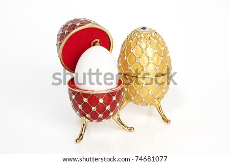 A red and a yellow jewel Easter egg with a real egg in the red one