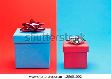A red and blue present in front of a red blue background - stock photo