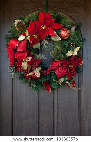 A red and green Christmas wreath on a wooden door - stock photo