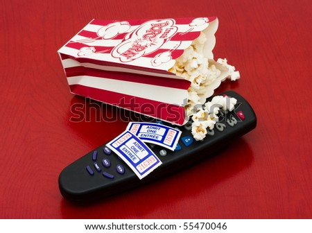 A red and white container of popcorn on a wood background, Home entertainment - stock photo