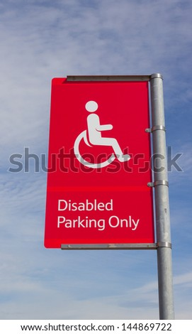 A red and white disabled parking sign, in the car park of a supermarket. Copyspace in sky. - stock photo
