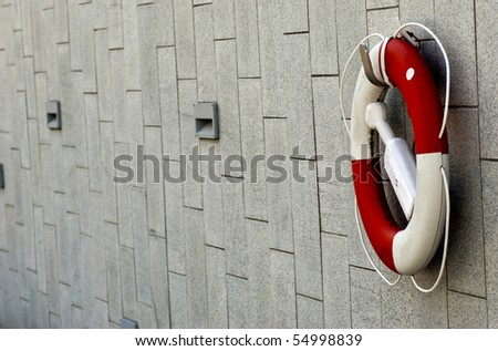 a red and white lifebuoy hanging on a stone wall - stock photo