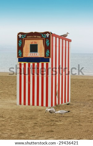 A red and white striped wooden punch and Judy booth on a beach located in Weymouth, Dorset UK.  A seagull perches on top, with two seagulls pecking at the sand below.