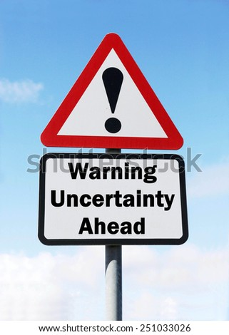 A red and white triangular road sign with a warning about uncertainty ahead concept against a partly cloudy sky. - stock photo