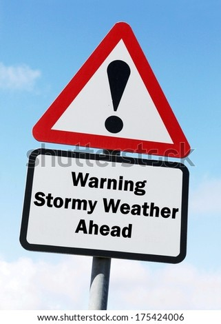 A red and white warning roadsign with a Stormy Weather ahead concept. against a partly cloudy sky background - stock photo