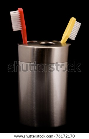 A red and yellow toothbrush in a holder on a black background. - stock photo