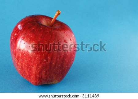 A red apple on blue background. - stock photo