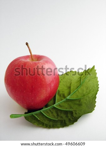 A red apple with a green leaf - stock photo