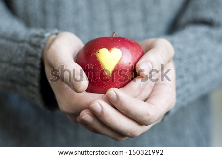 a red apple with a heart mark in man's hands