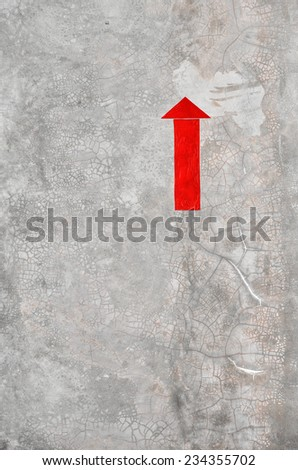 A red arrow on concrete cement wall - stock photo