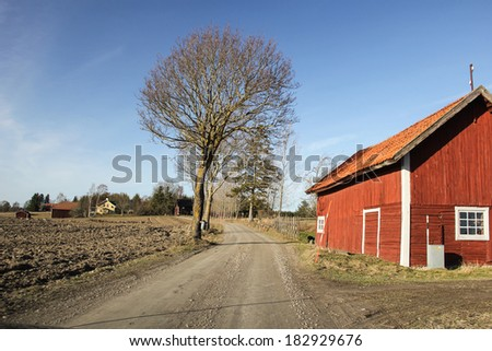 A red barn along a lonely dirt road in the Swedish countryside. - stock photo