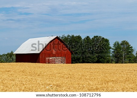 A red barn with a wagon in front and hay field in the foreground - stock photo