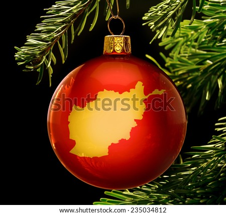 A red bauble with the golden shape of  Afghanistan hanging on a christmas tree isolated on black.(series) - stock photo