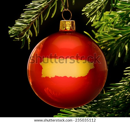 A red bauble with the golden shape of  Puerto Rico hanging on a christmas tree isolated on black.(series) - stock photo