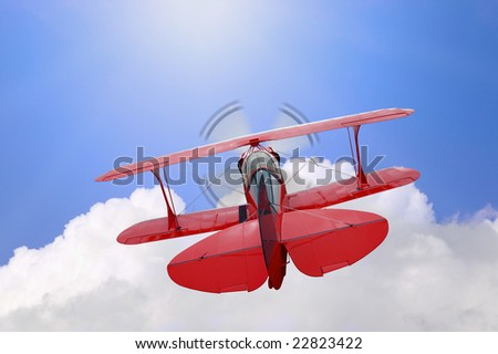 A red biplane flying high above the clouds towards the sun, concept image for the phrase Flying high - stock photo