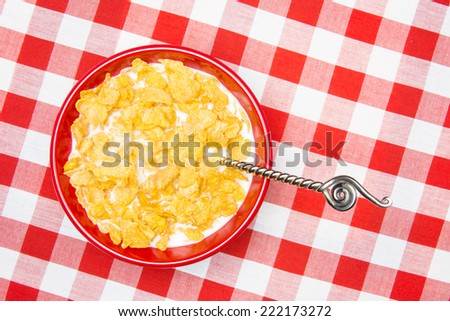 A red bowl of cornflakes and milk on a classic, red, checkered tablecloth ready as a breakfast meal.  - stock photo