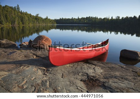 A red canoe rests on a rocky shore of a calm blue lake in the Boundary Waters of Minnesota