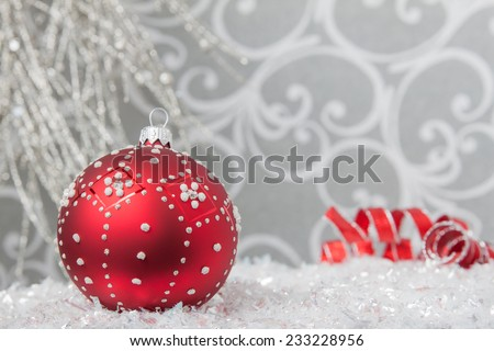 A red Christmas ornament in a silver backdrop with glittery snow