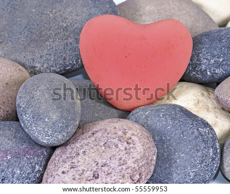 a Red colored stone heart surrounded by other natural stones - stock photo