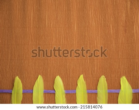 A red crepe paper background with 1 blue line at the bottom and 6 yellow feathers at the bottom, laying vertically and aligned - stock photo