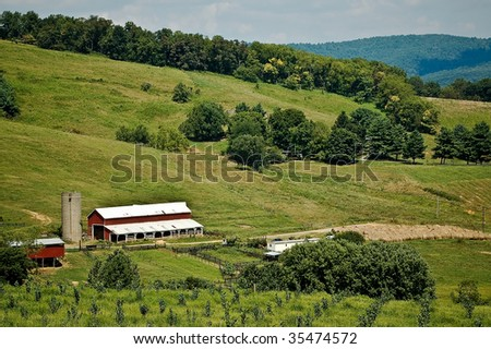 A Red Farm House Nestled Among Hills Sits On Expansive Green Farmland - stock photo