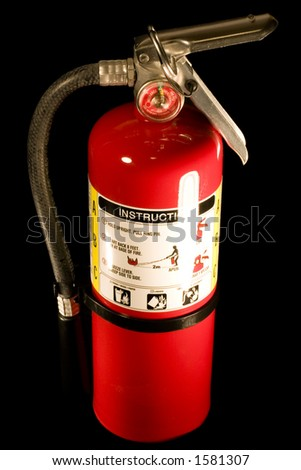 A red fire extinguisher isolated on a black background - stock photo