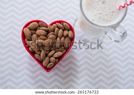 A red heart shaped bowl full of almonds with a glass of almond milk - stock photo