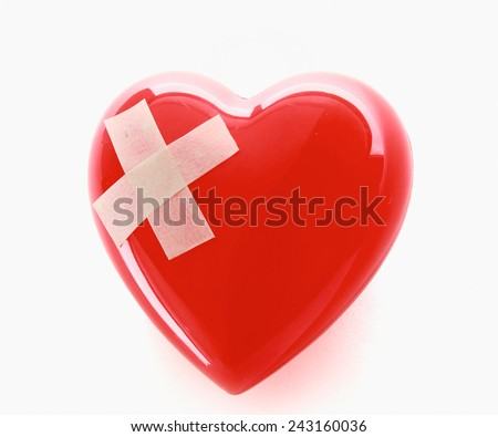 A red heart with adhesive plaster isolated on white background - stock photo