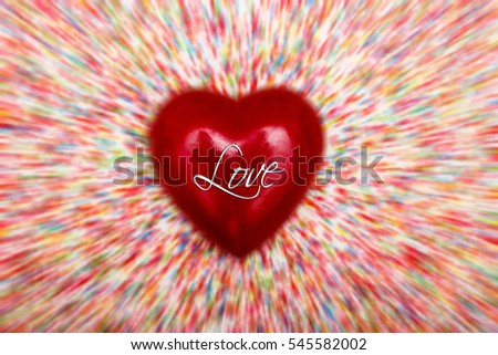 A red heart with the word Love, against a blurred background