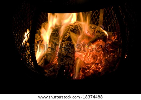A red hot fire burning in a backyard chimney with red glowing embers. - stock photo
