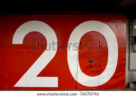 a red japanese tsunami watertight door in osaka bay area with the number 20 painted on it - stock photo