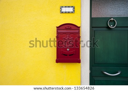 A red letterbox on a yellow wall,near a green door