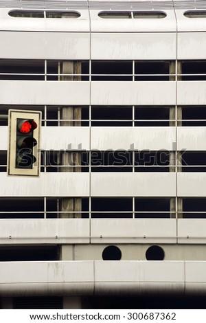 A red light is facing a striking facade made of metal / Traffic light in front of metal facade                - stock photo