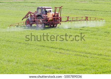 A red old tractor fertilizes a green field in spring - stock photo