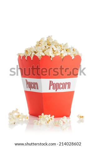 A red paper cups with popcorn, with some popcorn on the table. - stock photo