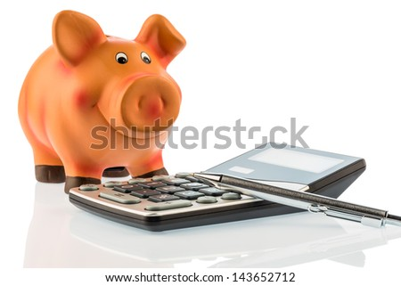 a red pen is on a calculator beside a piggy bank. save on costs, expenses, and budget. interest for savers - stock photo