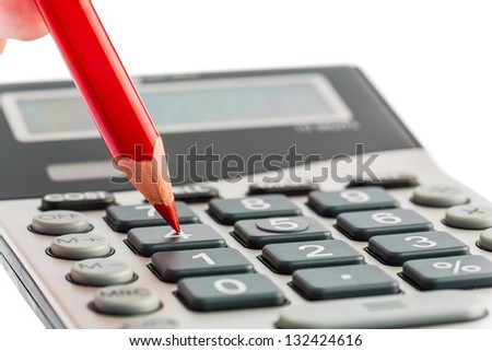 a red pen on a calculator. save on costs, expenditures and budget for bad economy - stock photo