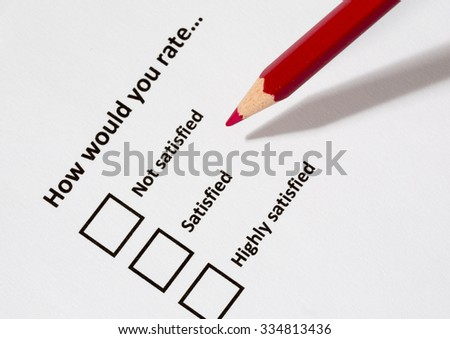 A red pencil against a survey form paper. It is asking how the person would rate the service he or she had. The focus point is in the pen tip. - stock photo