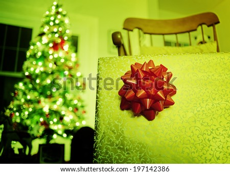A red ribbon decoration in selective focus, with a lit Christmas tree in the background. - stock photo