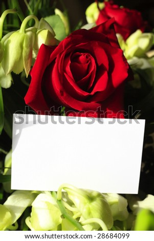 A red rose and orchids with a blank white card for a message - stock photo
