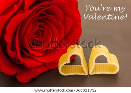 a red rose and two hearts against a dark background - stock photo