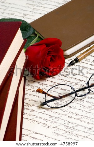 A red rose lays on top of a hand written document with a pile of books - stock photo
