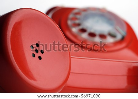 a red rotary dial telephone off the hook - focus on the receiver - stock photo